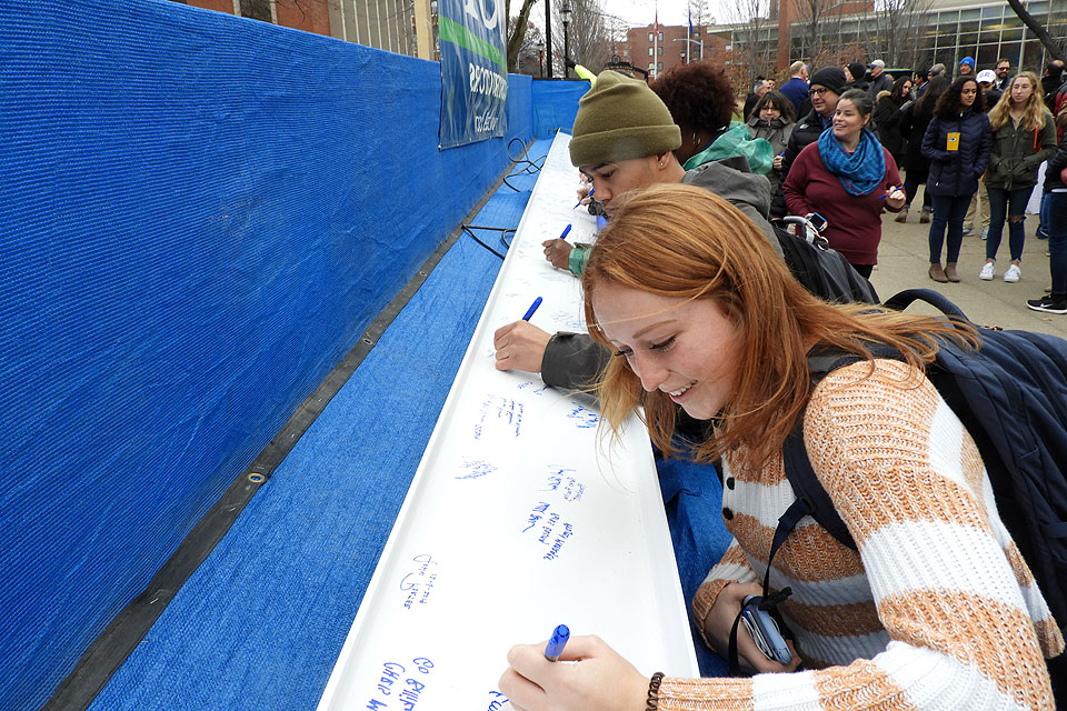 Students sign 该 beam to top out SLU's new ISE Building.