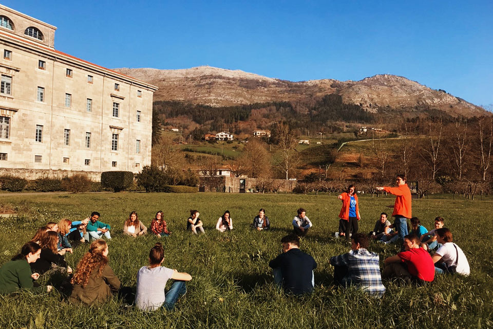 retreatants收集团契对SLU,马德里的洛约拉ignatian朝圣片刻 Retreat with the hills of Spain's Basque Country in the background. The students and retreat leaders are circled around a standing leader who is giving them instructions.