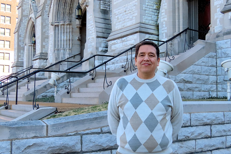 SLU sociologist Ness Sandoval, Ph.D., stands on the steps of St. Francis Xavier College Church.